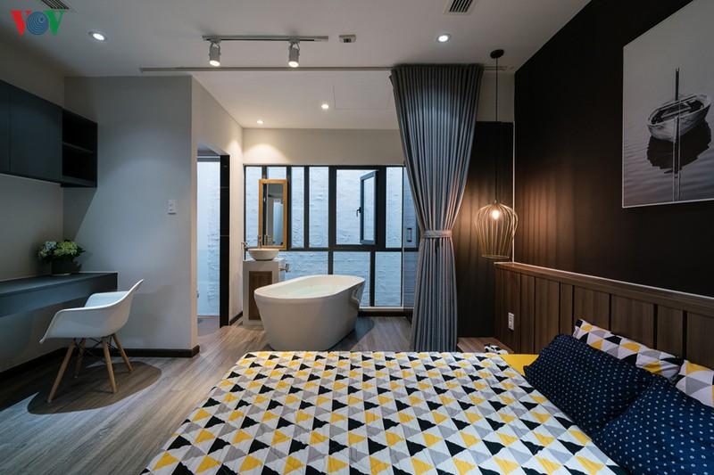 Phòng ngủ master nằm ở phía sau nhà, mở ra khoảng giếng trời. Đồ nội thất kết hợp màu xám với màu nâu gỗ.