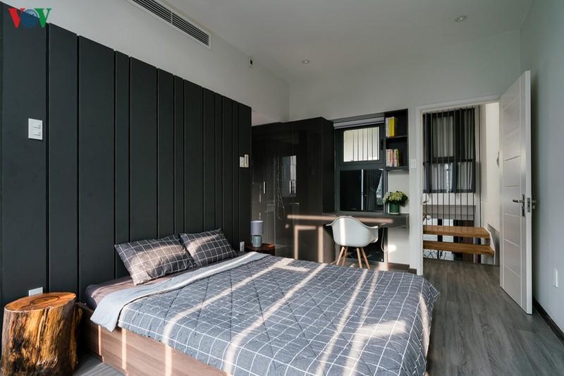 Một phòng ngủ khác nằm ở phía trước nhà. Mảng tường đầu giường được sơn màu xám sẫm, sàn gỗ màu xám nhạt.