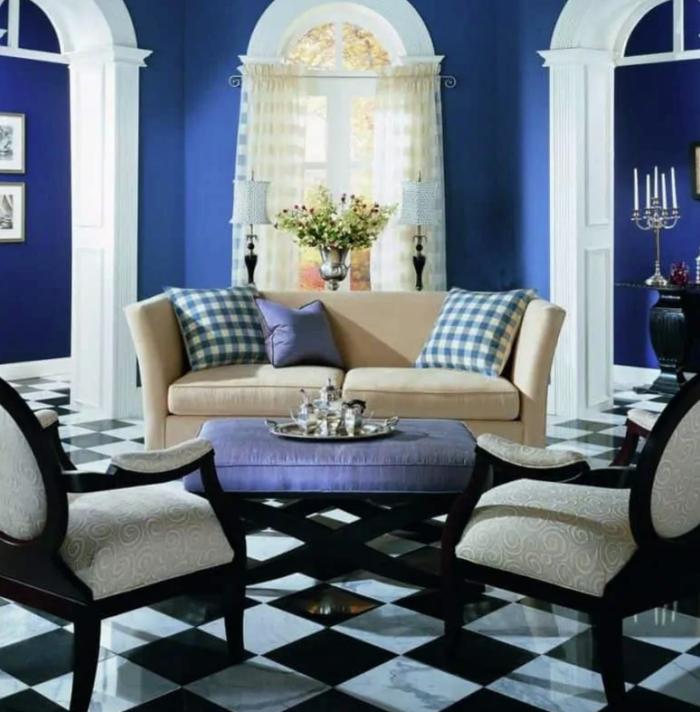 Một phòng khách nhỏ với tường màu xanh việt quất, sàn nhà màu trắng- đen