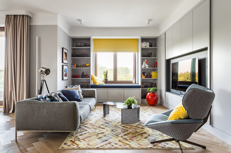 Đầu tiên là phòng khách, một tấm thảm sọc màu trung tính cân bằng các tông màu sáng bên trên