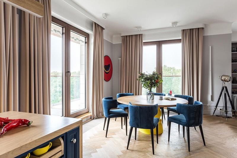 Phía sau phòng khách là bàn ăn. Những chiếc ghế ăn màu xanh bao quanh chiếc bàn ăn bằng gỗ.