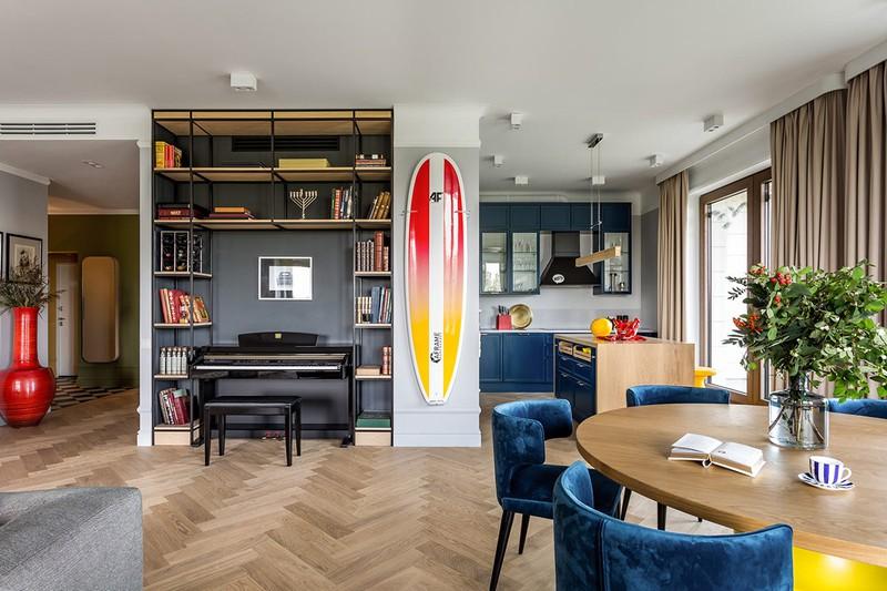 Giá sách ôm trọn đàn piano trong phòng khách, cạnh đó là ván lướt sóng treo tường nhằm phục vụ mục đích giải trí.