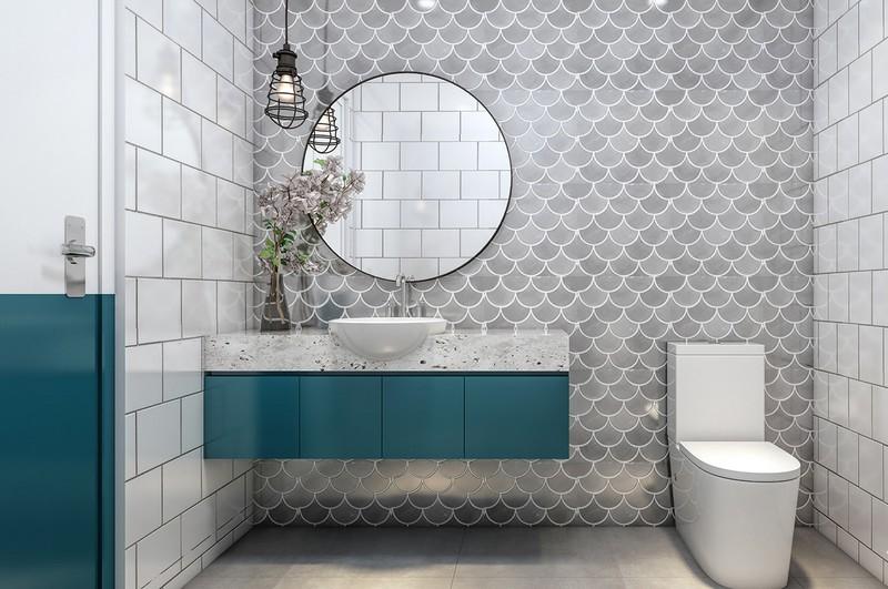 Bức tường hình vảy cá cùng kệ màu xanh tạo nên sự hài hòa cho phòng tắm