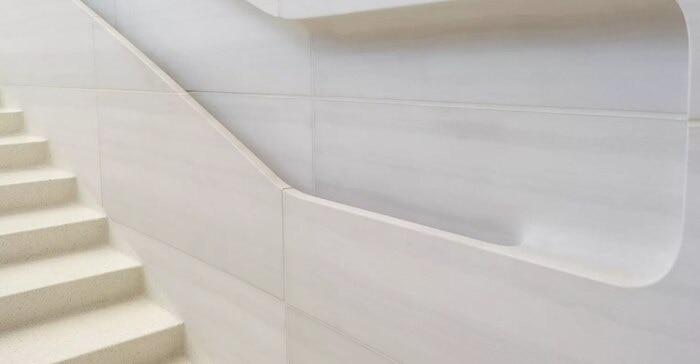 Tay vịn cầu thang được khắc trực tiếp bằng đá. Một điểm bất ngờ thú vị là phần lòng bàn tay bạn chạm vào để vịn, tiếp xúc sẽ được thiết kế nhám trong khi đó ở mặt bên trong, nơi những ngón tay bạn trượt khi di chuyển, lại được thiết kế mịn. Đây thực sự là một chi tiết cho thấy Apple tỉ mỉ đến mức nào với công trình này.