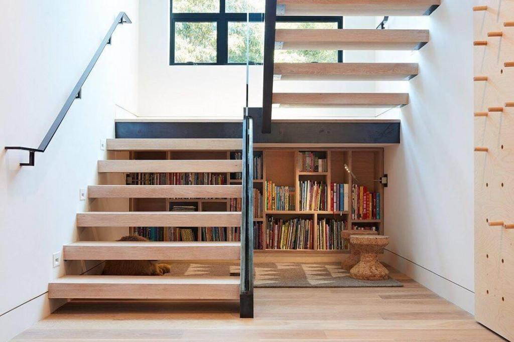 Tủ sách ngay dưới gầm cầu thang giúp các thành viên có thể tiếp cận sách bất cứ lúc nào