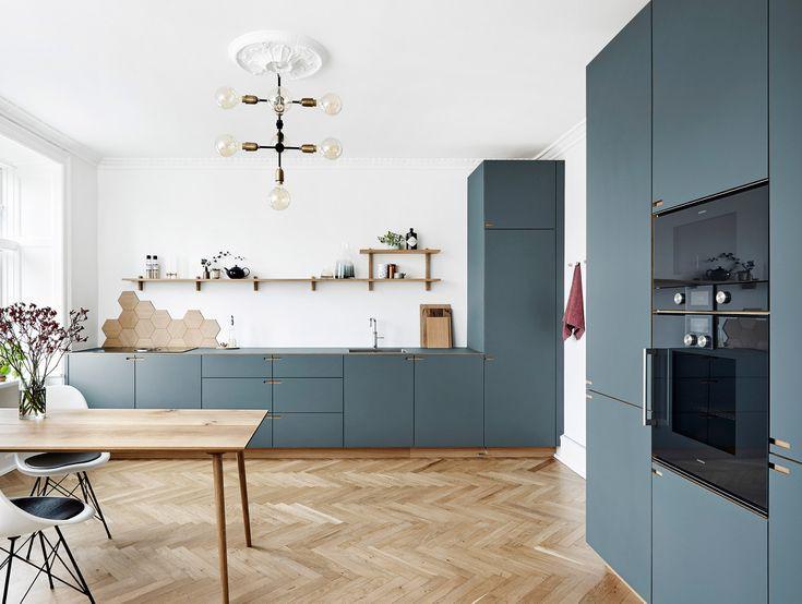 Phòng bếp kiểu Đan Mạch với tủ bếp màu xanh xám thiết kế tinh tế theo phong cách tủ đựng đồ, mang đến cảm giác ấm cúng. Tường chắn bếp (backsplash) lát bằng gỗ hình lục giác tạo điểm nhấn thú vị cho tường màu trắng.