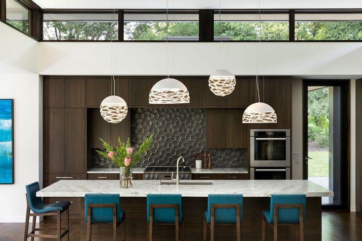 Phòng bếp duyên dáng với tủ bếp làm bằng gỗ tối màu khá giống nội thất phòng khách cùng tường chắn bếp lát gạch 3D đẹp mắt. Thiết kế đèn độc đáo theo phong cách sợi dây chuyền mang lại sự sang trọng cho phòng bếp.