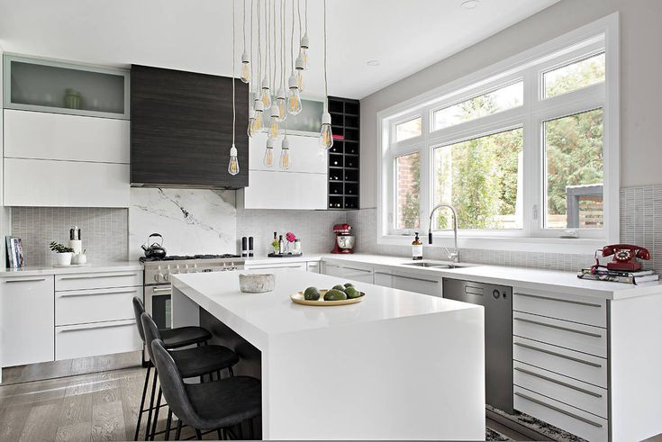 Phòng bếp trang trí màu trắng vô cùng hiện đại nhờ tủ bếp thiết kế sáng bóng và đảo bếp bằng đá thạch anh có bồn rửa. Tường chắn lò nướng lát gạch xám và tủ bếp bằng gỗ màu tối tạo điểm nhấn cho không gian màu trắng nhờ sắp đặt và họa tiết thú vị.
