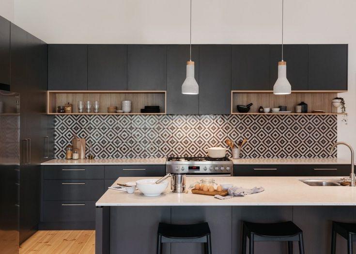 Tủ bếp làm bằng chất liệu gỗ được sơn đen mang đến nét mới lạ cho phòng bếp hiện đại. Tường chắn bếp lát gỗ họa tiết hình học nổi bật mang đến sự độc đáo cho không gian bếp.