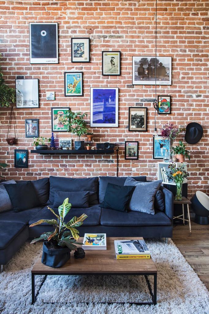 Một chiếc ghế sofa hiện đại, màu xanh tương phản với những viên gạch đỏ. Một tấm thảm làm cho căn phòng sang trọng và ấm cúng