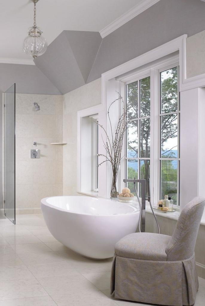 Trong không gian màu sắc khá trung tính với chiếc bồn oval màu trắng, bình hoa, chiếc ghế đệm màu xám giúp cân bằng và tạo cảm giác thư giãn