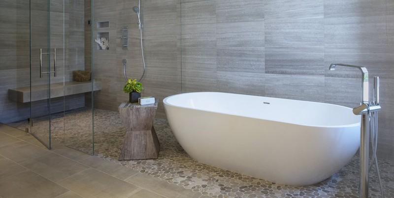 Thiết kế phòng tắm tối giản với chiếc bồn trắng làm nổi bật các vật liệu tự nhiên như tường gỗ, đôn gỗ và bình hoa nhỏ