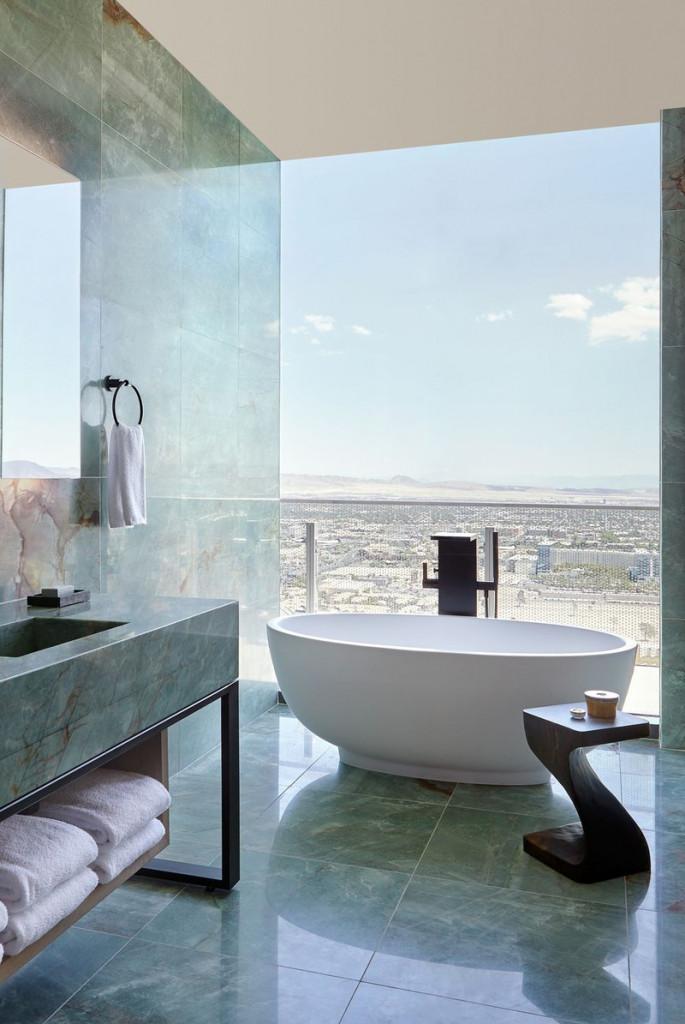Nổi bật trên lớp đá cẩm thạch xanh lá và phần tường kính là bồn tắm oval