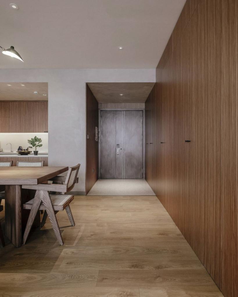 Cửa ra vào bằng gỗ đồng bộ với không gian mang đến sự mộc mạc, gần gũi, ấm cúng cho căn hộ của cặp vợ chồng trẻ