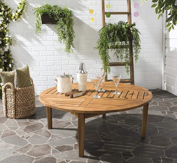Một kiểu bàn gỗ hình tròn đã qua xử lý để chống chịu được thời tiết bên ngoài