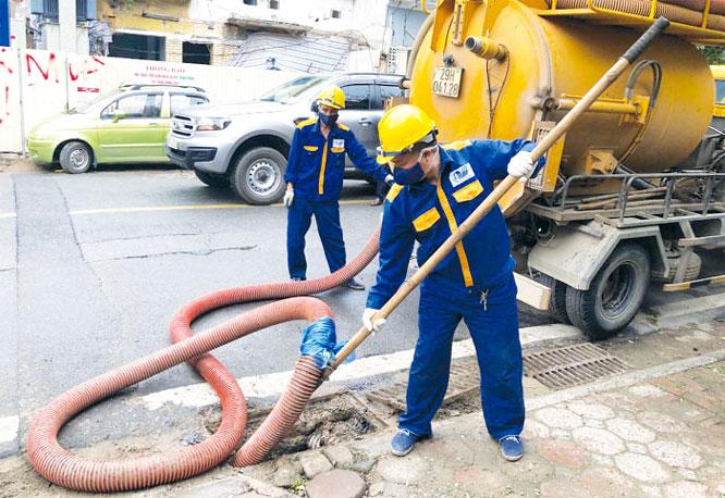 Công nhân Công ty Thoát nước nạo vét cống tại ngã ba Phan Bội Châu - Trần Hưng Đạo (gần Ga S12, thuộc Dự án đường sắt đô thị Hà Nội, đoạn Nhổn - Ga Hà Nội)