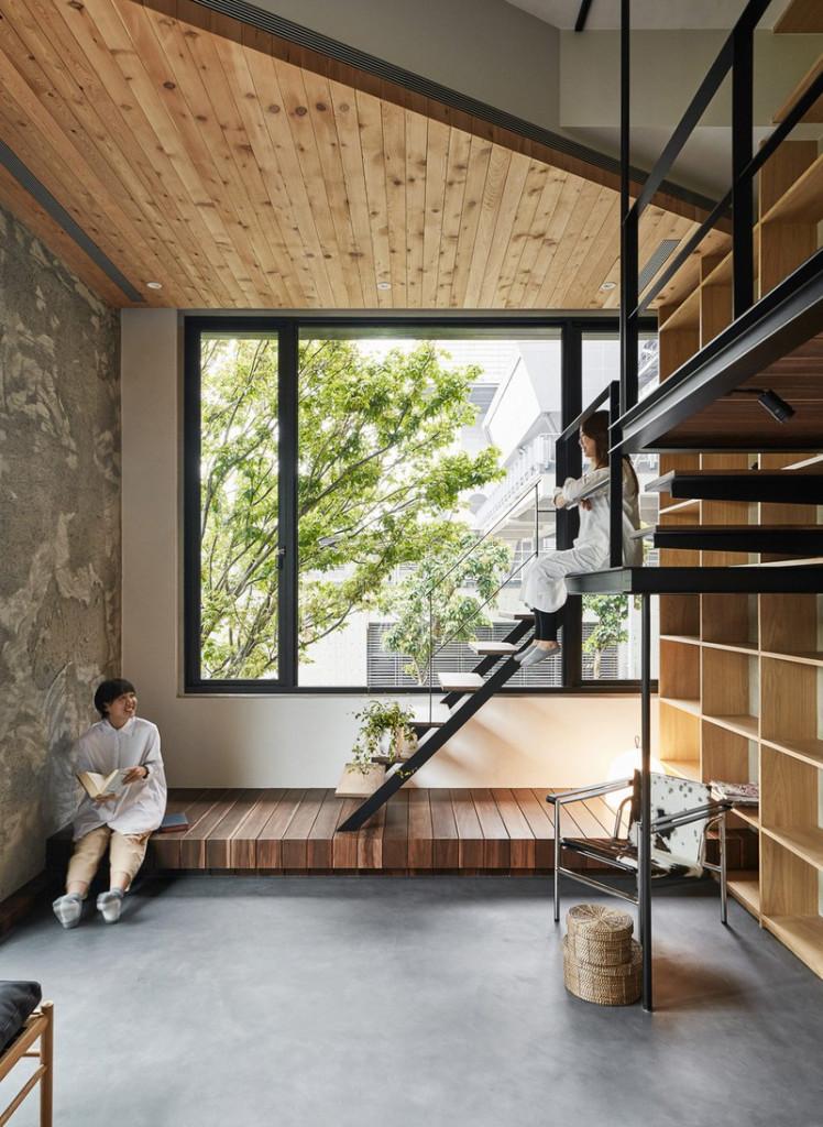 Cầu thang bằng sắt kết nối phòng khách với 2 phòng ngủ. Một bục gỗ để nổi, đóng vai trò như một chiếc ghế để ngồi trò chuyện.