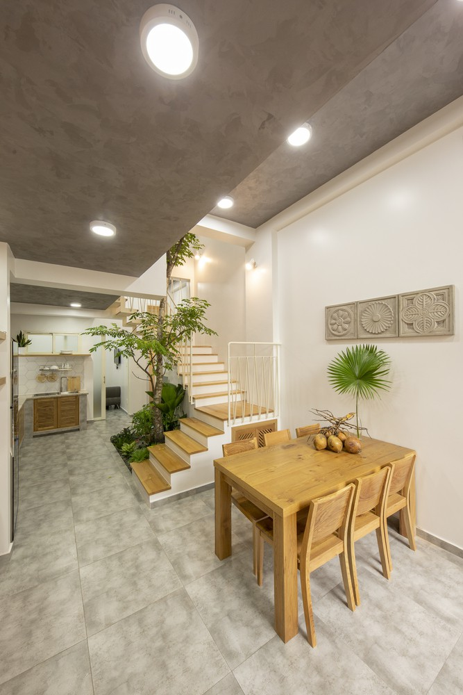 Giữa nhà là cầu thang đi xung quanh cây lớn dưới một mái nhà mờ, chức năng như mảng xanh đem lại sự thoáng mát