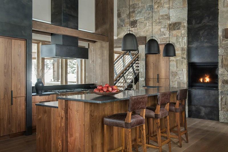 Căn phòng bếp gỗ mang hơi hướng rustic với tường đá, đèn trang trí kim loại, bàn đá cẩm thạch ấn tượng