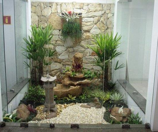 Sân vườn nhỏ theo phong cách Nhật Bản có đèn đá, đá sỏi và cây xanh.