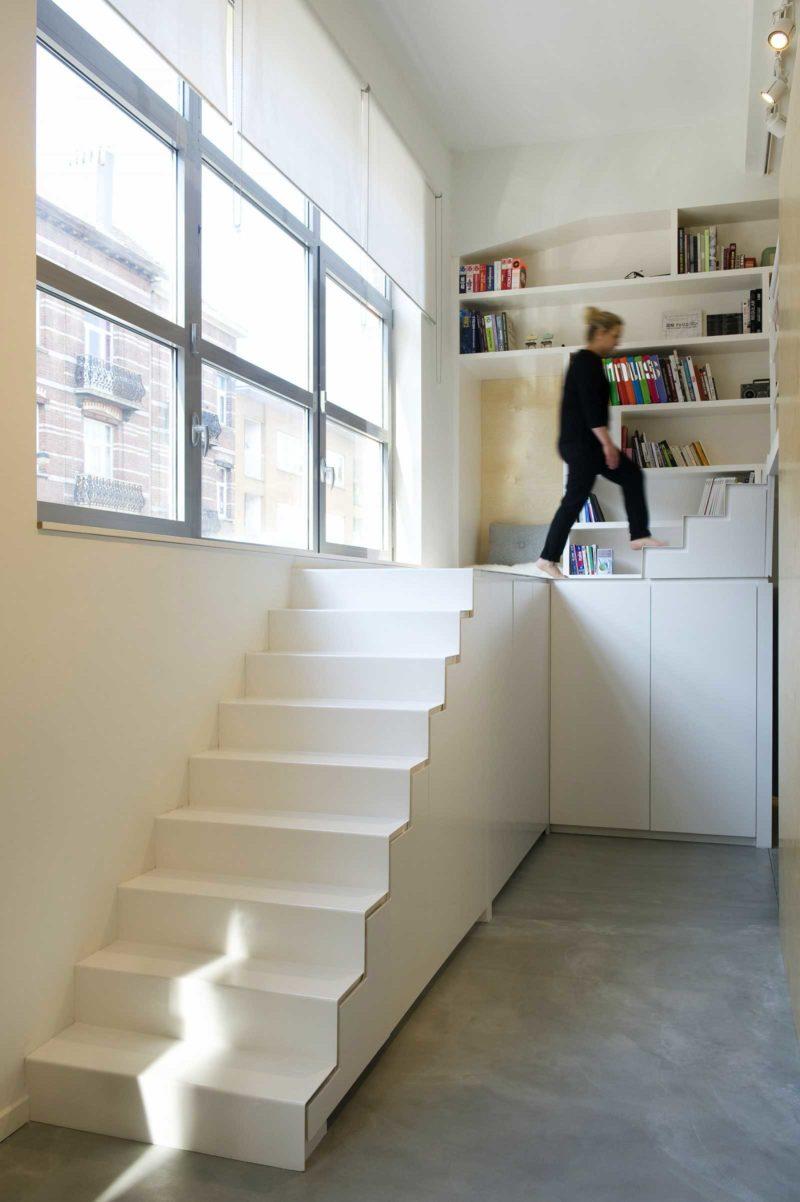 Cầu thang màu trắng có tích hợp với những ngăn tủ phía dưới gầm giúp căn phòng tăng thêm diện tích lưu trữ, đồng thời mang đến cuộc sống thoải mái, vui vẻ, tiện lợi.