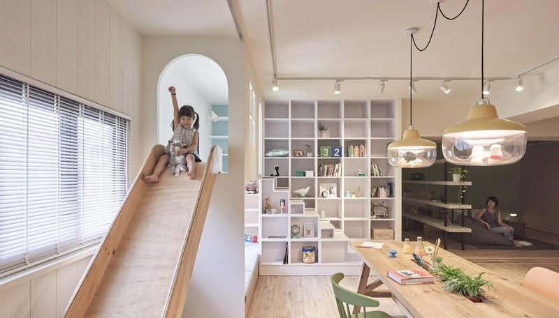 Tủ sách và máng trượt đặt trong cùng một không gian để bé vừa học lại có thể vừa chơi