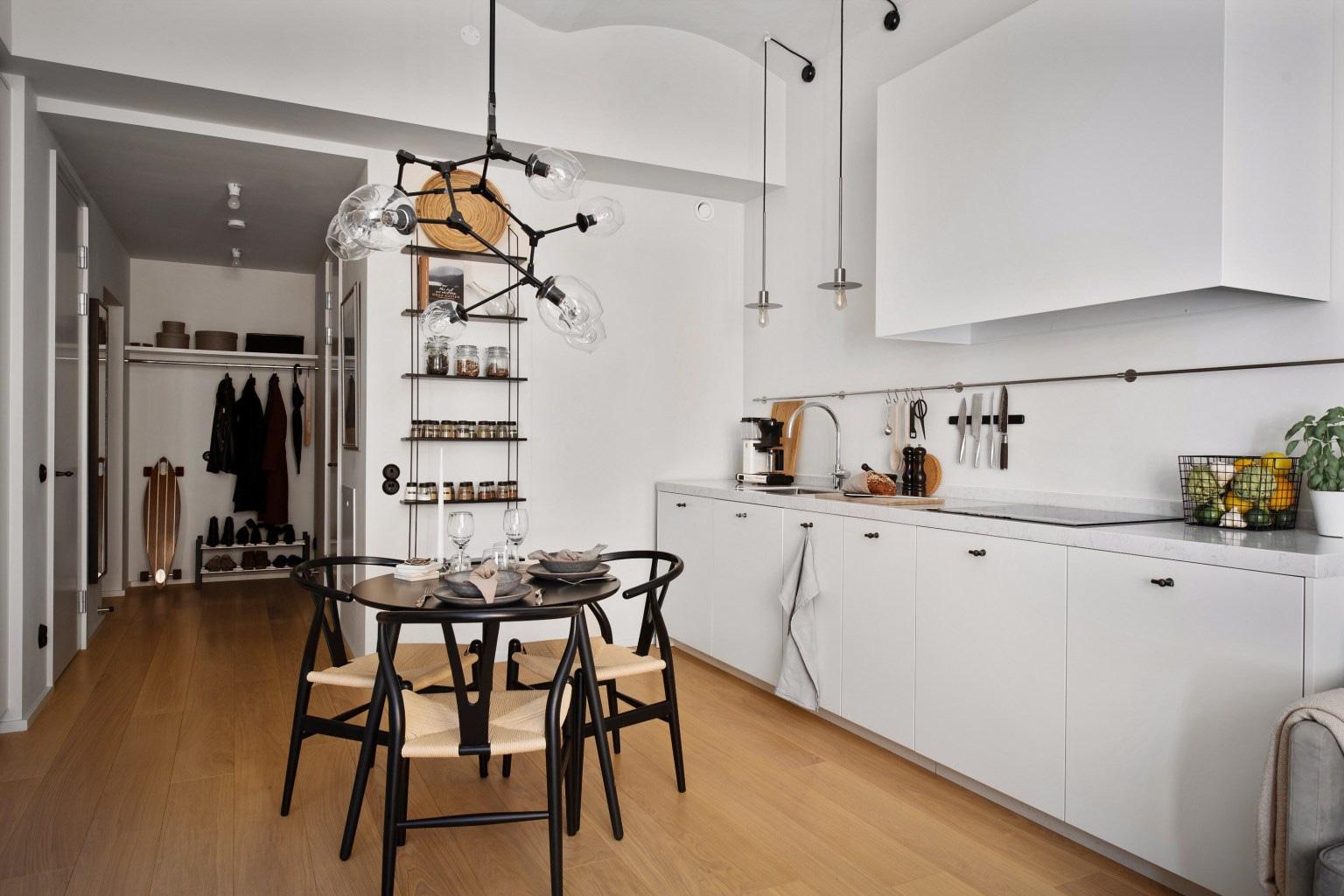 Góc bếp được tận dụng bố trí ở khoảng tường chạy dọc từ lối vào đến phòng khách. Hệ tủ dưới màu trắng được thiết lập giúp không gian trở nên gọn gàng khi lưu trữ đồ đạc bên trong.