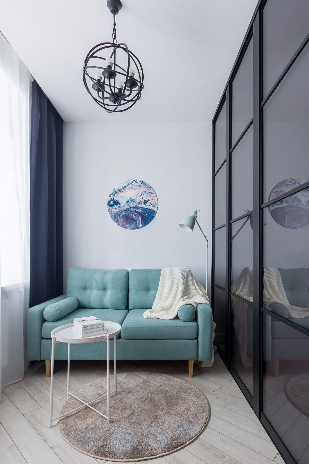 Phòng khách nhỏ với diện tích khá khiêm tốn nhưng vẫn vô cùng xinh xắn và đủ đầy khi được đặt sofa nhỏ gọn với màu xanh ngọc lam trẻ trung, bắt mắt