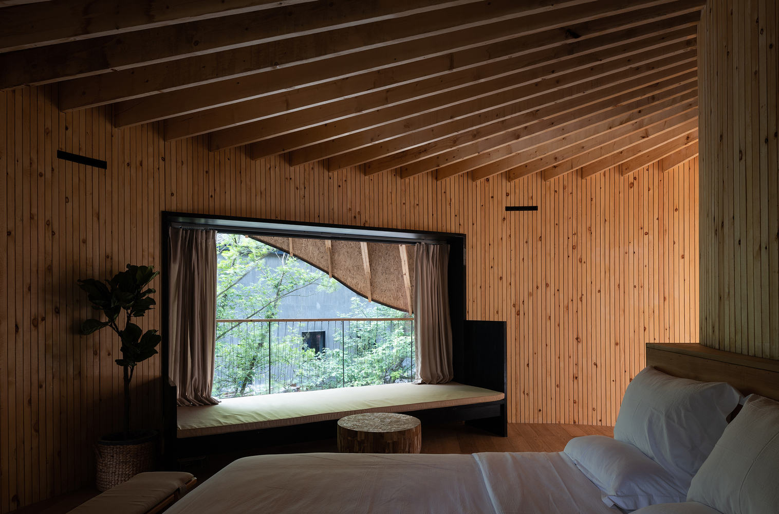Trong phòng ngủ, bệ cửa sổ được thiết kế ghế ngồi thư giãn, đọc sách, chiêm ngưỡng cảnh sắc thiên nhiên xanh mát bên ngoài.