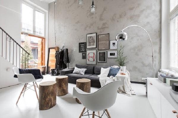 Màu xám trắng của mảng tường sơn hiệu ứng giả bê tông trong phòng khách đương đại tạo vẻ hài hòa với gam trắng chủ chủ đạo, tuy nhiên không kém phần nổi bật bởi các vết loang tự nhiên.