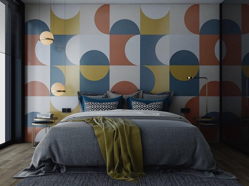 Một họa tiết hình tròn lặp đi lặp lại trên một bức tường đầu giường đầy màu sắc, hài hòa với ánh đèn.