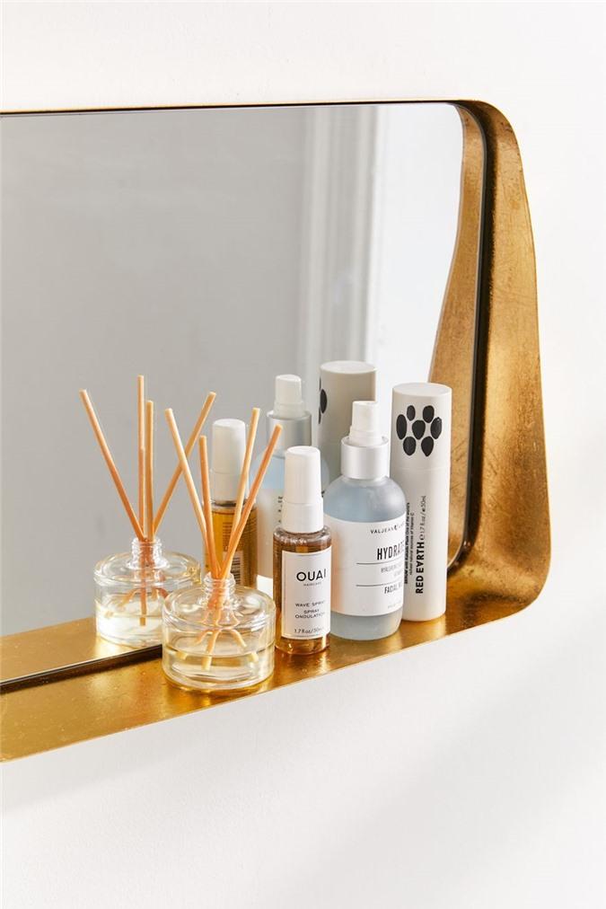 Một hiệu ứng cong được thực hiện bởi các cạnh tròn của chiếc gương có khung gỗ này là đặc trưng trong phòng tắm của Camille Styles. Đường viền bằng gỗ giúp thêm một chút phong cách trong không gian.