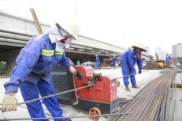 Công nhân làm việc tại đường Vành đai 3 dưới thấp qua hồ Linh Đàm. Ảnh: Thanh Hải