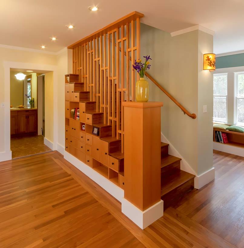 Vách ngăn cầu thang bằng các thanh lam thiết kế tỉ mỉ, tinh tế tích hợp thêm các kệ nhỏ lưu trữ, trang trí