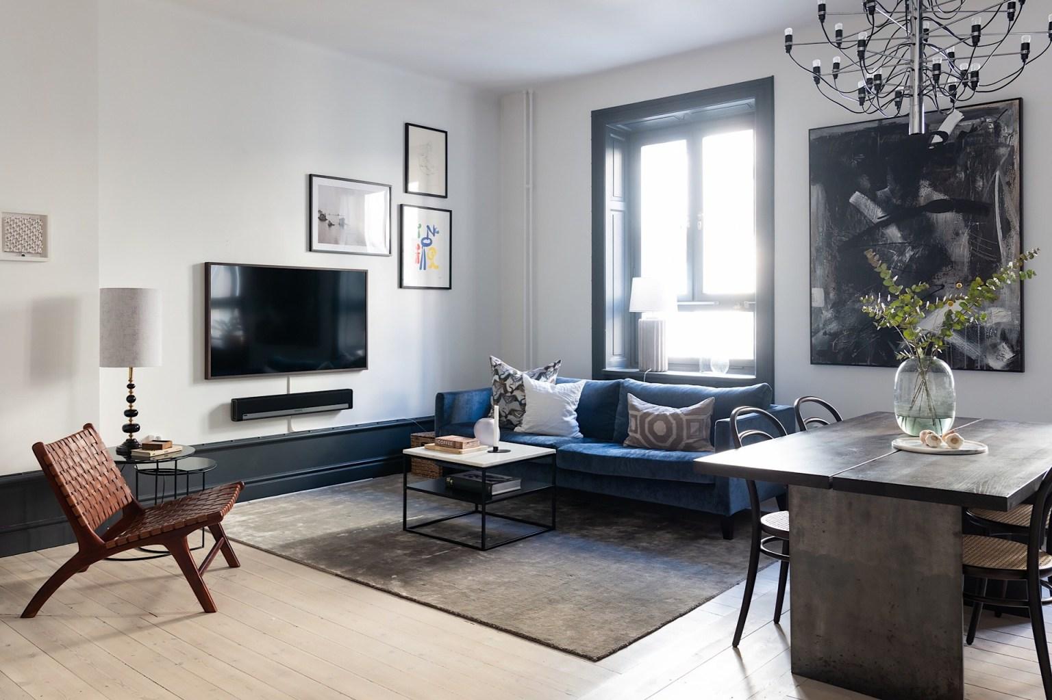 Sofa được lựa chọn màu xanh cổ vịt, sàn gỗ và tường màu trắng. Những màu nền tươi sáng giúp điểm nhấn trang trí màu đen thêm nổi bật sắc nét hơn.