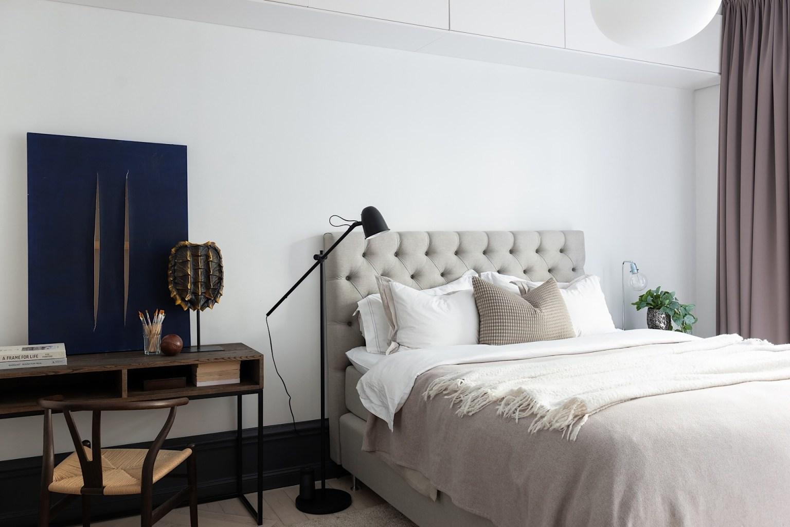 Giường ngủ đặt song song với khung cửa sổ, bên cạnh là bàn làm việc