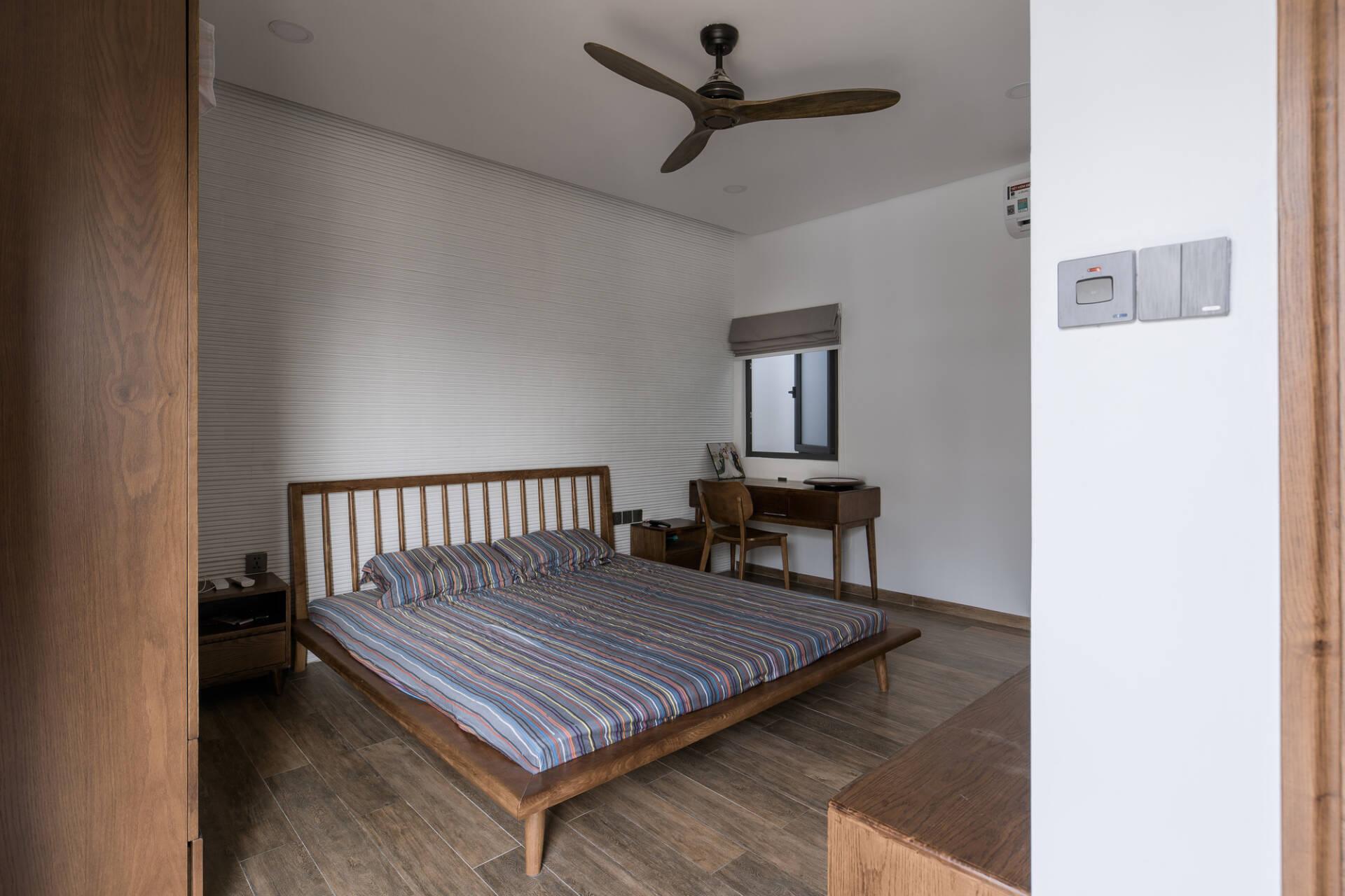 Với những phòng ngủ không có mặt thoáng hướng ra bên ngoài, KTS đã tận dụng khoảng giếng trời với ô cửa sổ nhỏ. Phòng không có nhiều đồ đạc và được sắp xếp gọn gàng