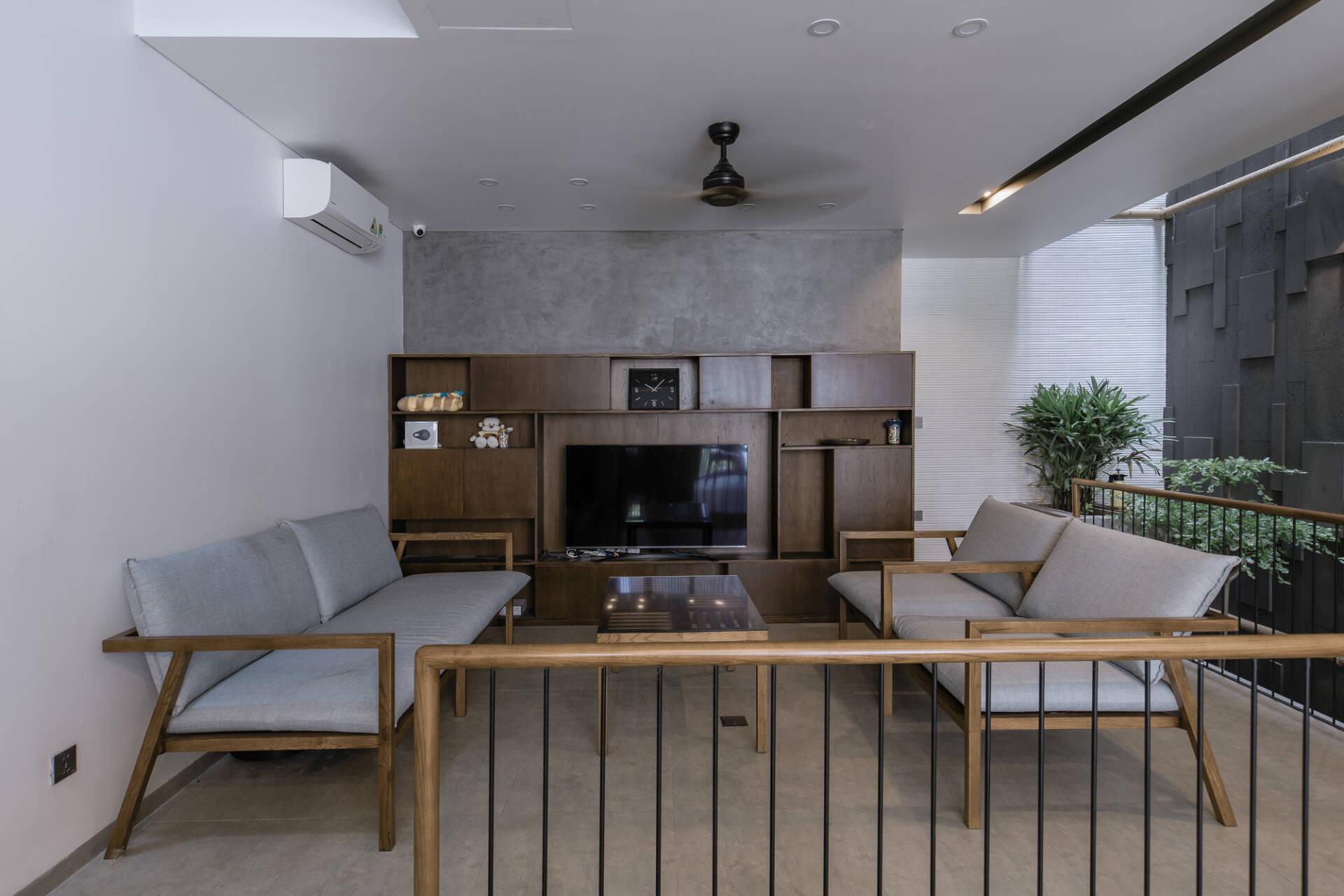 Phòng khách mộc mạc với một phần tường và sàn bằng bê tông. Đồ nội thất đơn giản nhưng ấm cúng