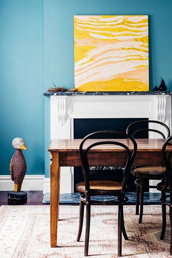 Bạn không cần phải sơn toàn bộ tường bằng màu cúc vạn thọ. Chỉ cần thêm tác phẩm nghệ thuật như ở trong phòng ăn này là có thể làm bừng sáng toàn bộ không gian.
