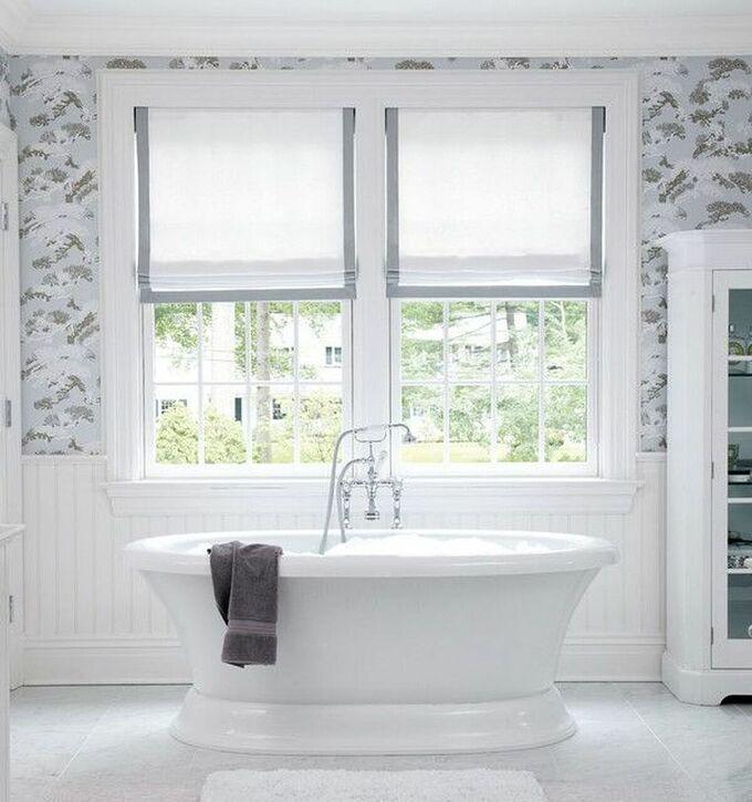 Phòng tắm hiện đại này sử dụng cửa sổ khung cửa màu trắng, bồn tắm cùng tông màu đặt cạnh cửa sổ giúp không gian sang trọng.