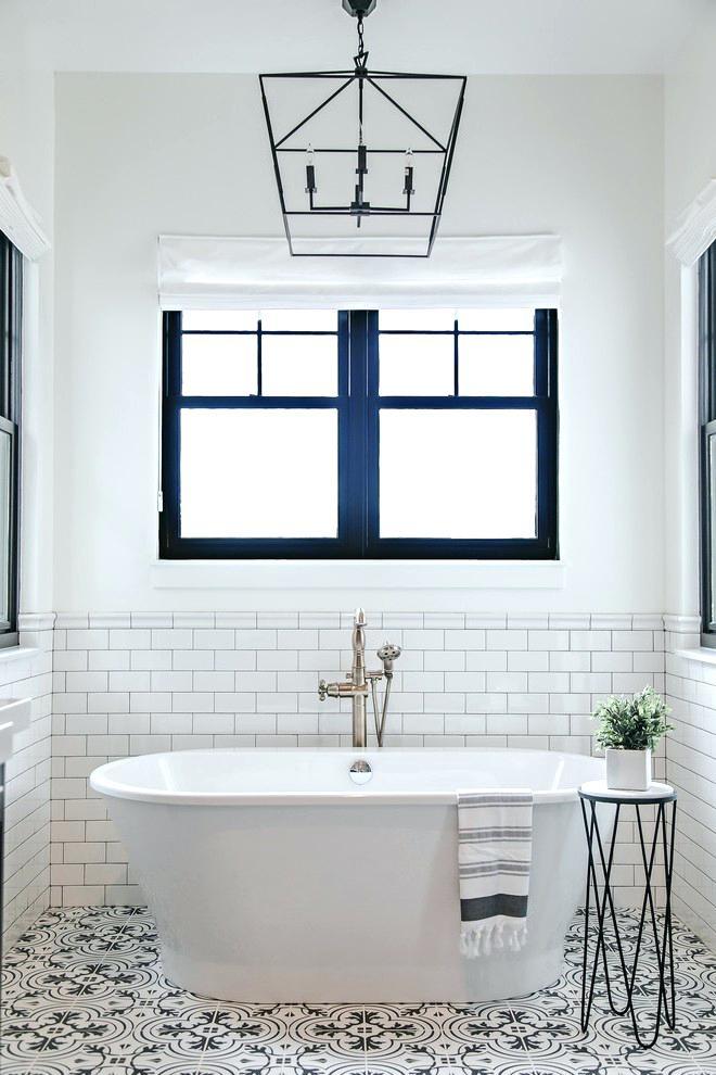 Không gian tắm nhỏ trông sáng sủa và rộng lớn hơn nhờ tông màu trắng. Cửa sổ đôi màu đen giúp đón ánh sáng tự nhiên, ngắm cảnh ngoài trời. Gạch lát nền có hoa văn bắt mắt, những chậu cây làm sống động căn phòng.