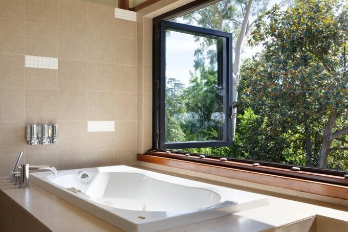 Bồn tắm bố trí gần cửa sổ hình khung đen cho phép gia chủ tận hưởng quang cảnh ngoài trời, không khí đầy nắng, mát mẻ.