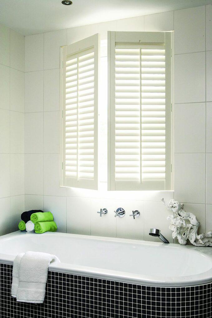 Cửa sổ chớp màu trắng trên bồn tắm có gạch mosaic màu đen tạo điểm nhấn cho không gian. Khăn màu xanh lá cây, xanh nước biển, trắng cuộn tròn đặt trên bồn tắm, tạo cảm giác như một phòng tắm spa.