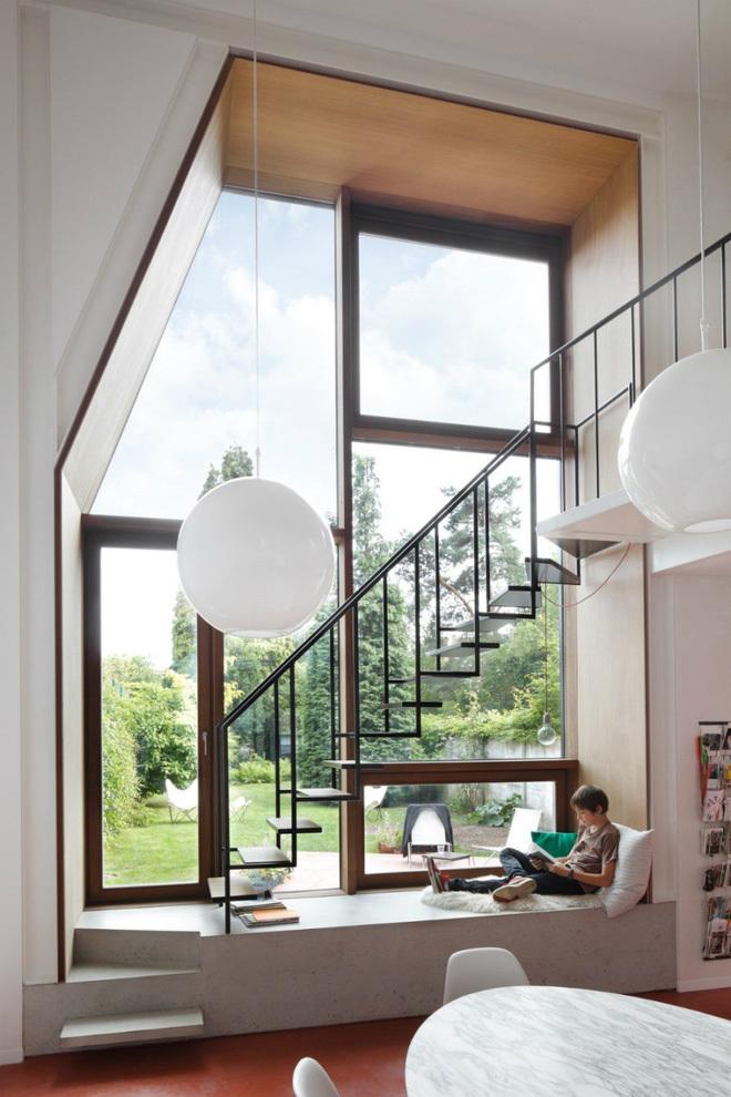Gia chủ khéo léo tận dụng khoảng trống nhỏ dưới gầm cầu thang phòng khách làm nơi thư giãn, đọc sách hướng tầm nhìn ra cảnh quan xanh mát bên ngoài