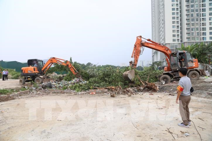 Huyện Thanh trì huy động phương tiện cơ giới thực hiện cưỡng chế giải phóng mặt bằng để xây dựng khu tái định cư Tây Nam Kim Giang. Ảnh Mạnh Khánh-TTXVN