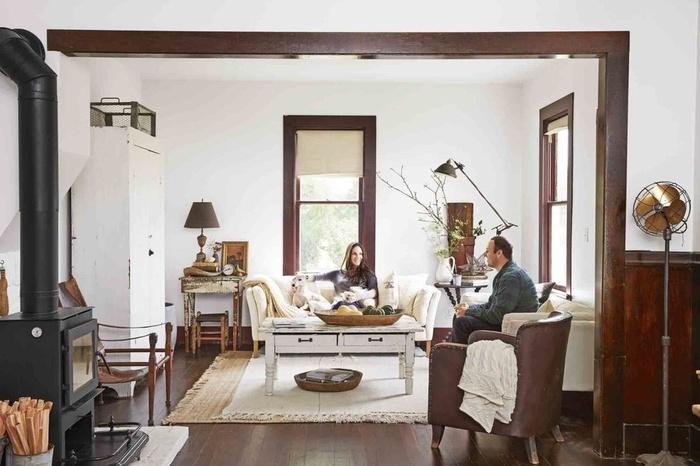 Mặc dù có sàn gỗ cứng sẫm màu và chiếc ghế bọc da màu nâu cổ kính vẫn mang lại cảm giác nhẹ nhàng và tươi sáng cho phòng khách nhờ cửa sổ cao, ghế sofa vải lanh và thảm màu trắng