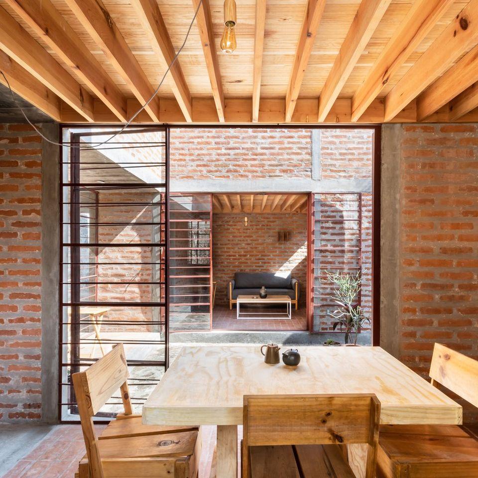 Hai phòng khách và phòng ăn nằm đối diện nhau bởi hai chái thông qua sân nhỏ.