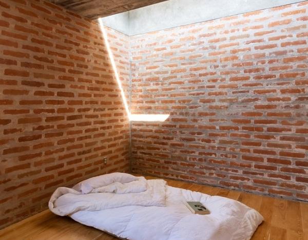 Nếu như khu vực tầng trệt được thiết kế làm khu vực tiếp khách, bếp, sân trong và khu ăn uống thì tầng trên là khu vực riêng tư như phòng ngủ, phòng làm việc và phòng vệ sinh. Phòng ngủ khá đơn giản bởi một chiếc đệm trắng cùng giếng trời mang ánh sáng chiếu rọi căn phòng.