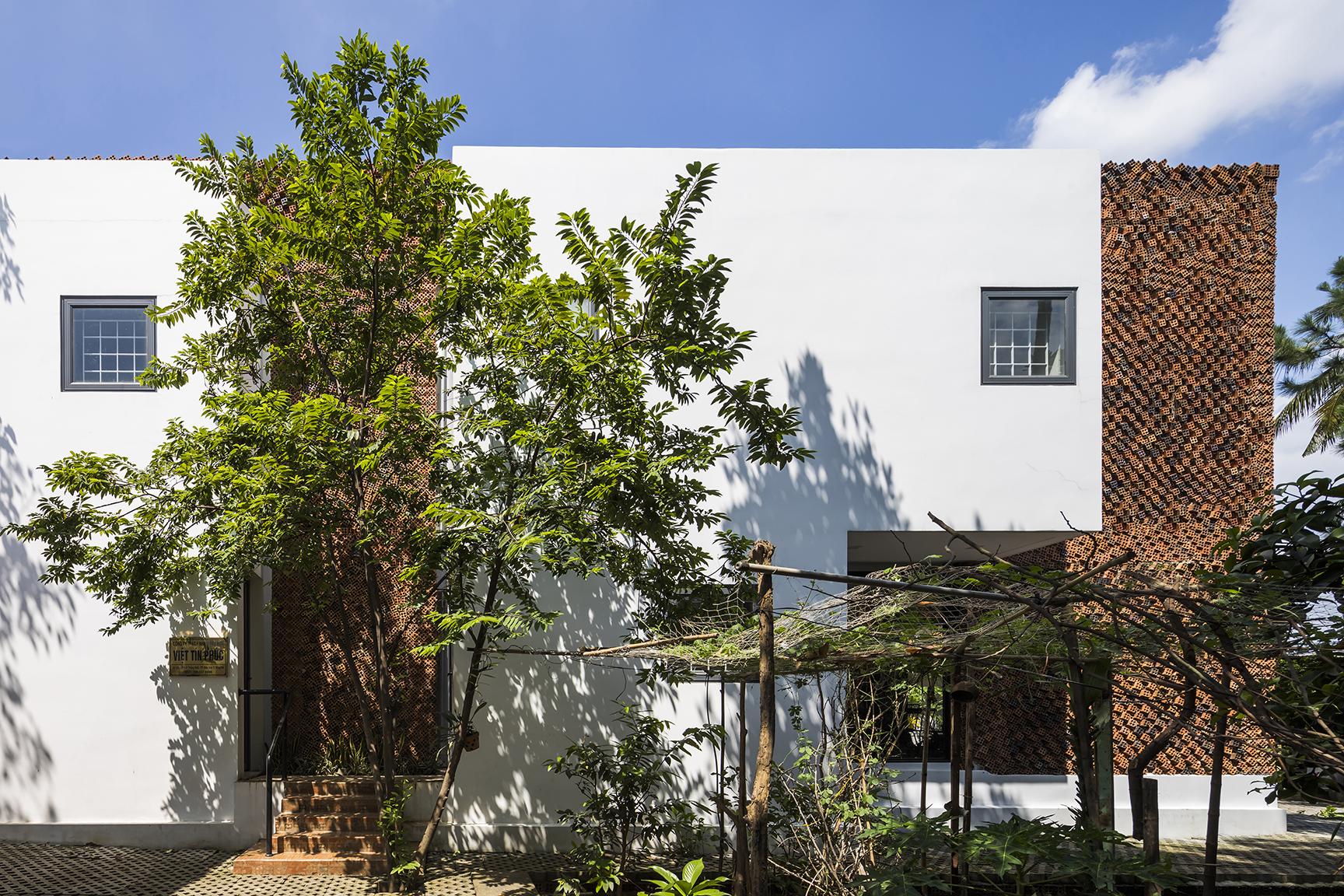 Cây xanh sân vườn và bức tường gạch là hai lớp áo giúp làm mát ngôi nhà
