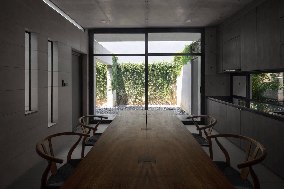 Bếp và phòng ăn nhìn ra sân sau với bức tường dây leo xanh mát